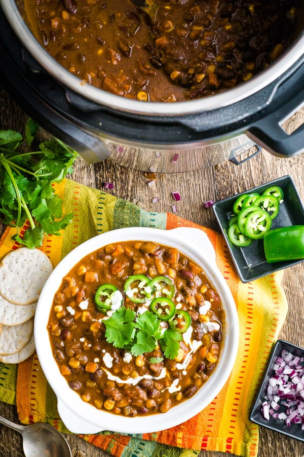 vegan chili in white bowl on festive cloth napkin with jalapeno, cilantro, and cracker garnish with vegan chili in the Instant Pot