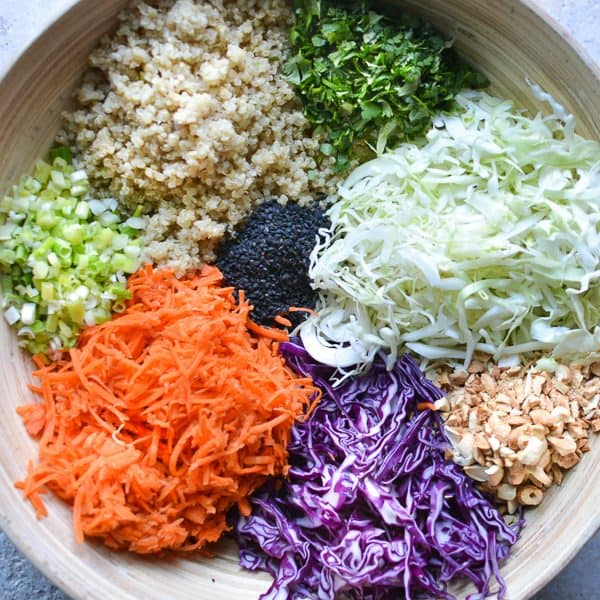 bamboo bowl of Asian slaw ingredients placed in individual piles