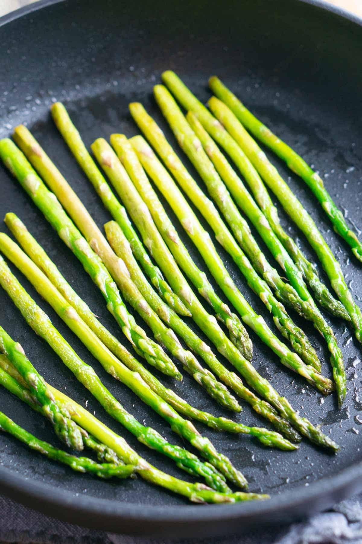 sauteed asparagus in black skillet