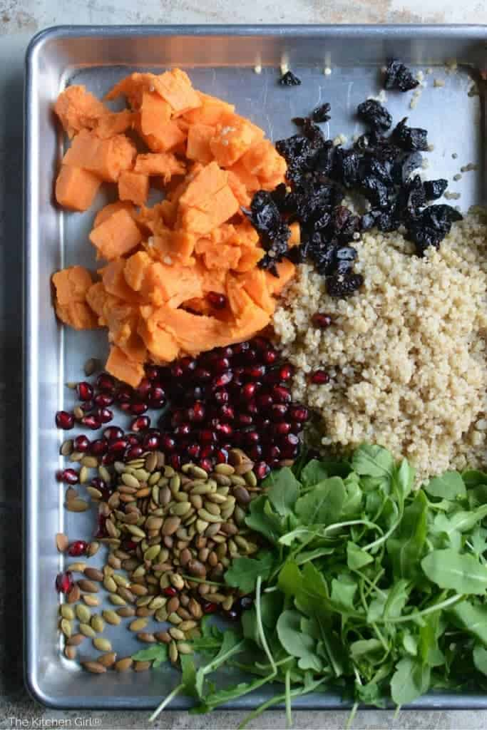 arugula, cooked quinoa, dried cherries, diced sweet potato, pomegranate, and toasted pumpkin seeds on baking sheet