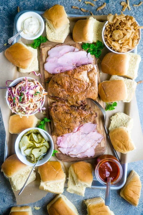 pork slider bar with pork roast in the center surrounded by toppings (coleslaw, bbq sauce, pickles, mayonnaise, and French fried onions) and scattered slider rolls