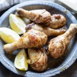 baked chicken legs and lemon wedges on blue enameled plate on grey background