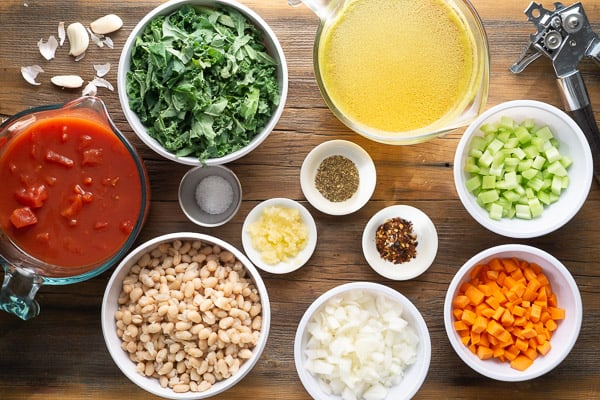 White bean kale soup ingredients on brown wood surface (individual bowls of diced tomatoes, fresh kale, chicken broth, diced celery, diced carrots, diced onions, white beans, minced garlic, and seasonings)