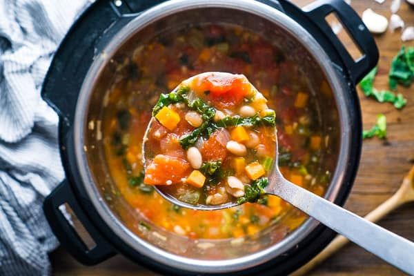 Stainless steel ladle of white bean and Kale soup over Instant pot full of soup on wood surface with blue linene and parsley garnish