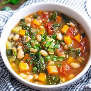 White bean kale soup in white bowl on seersucker linen with parsley garnish