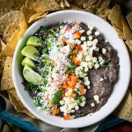 loaded black bean dip in white bowl surrounded by tortilla chips and multicolored background