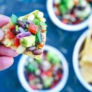 tortilla chip in hand with black bean and corn salsa over blue background and white bowls of salsa and tortilla chips