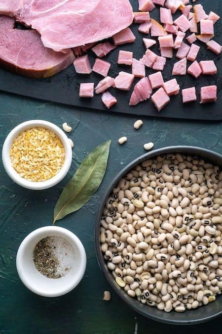 black eyed peas recipe ingredients (diced ham, black eyed peas, dried onion, salt and pepper, and bayleafon green background