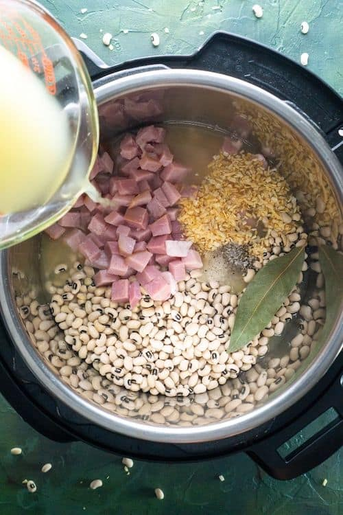 Image of chicken broth being poured over black eyed peas ingredients in the Instant pot