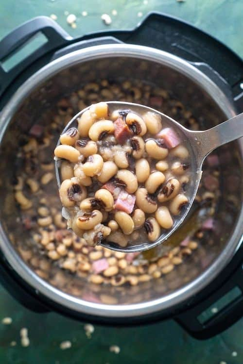 ladle of black eyed peas over instant pot on green background