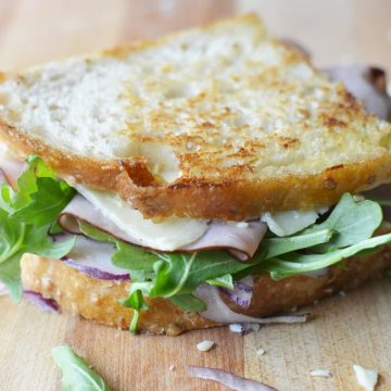 Grilled cheese for grown ups on game day! Sliced sourdough, garlic mayo, Black forest ham, white cheddar, fresh arugula, and red onion. Black Forest White Cheddar Panini on thekitchengirl.com