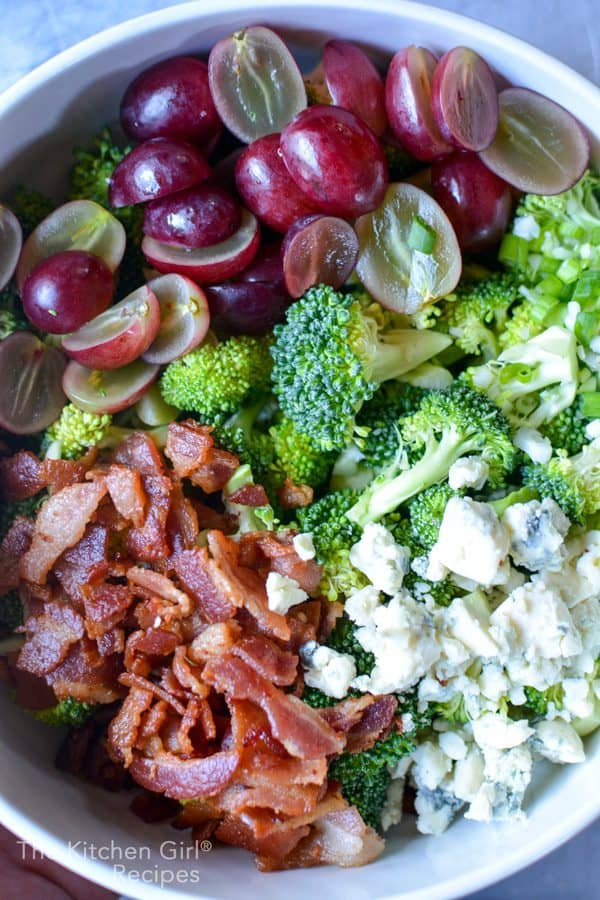 broccoli, bacon, red grapes, and blue cheese in white bowl