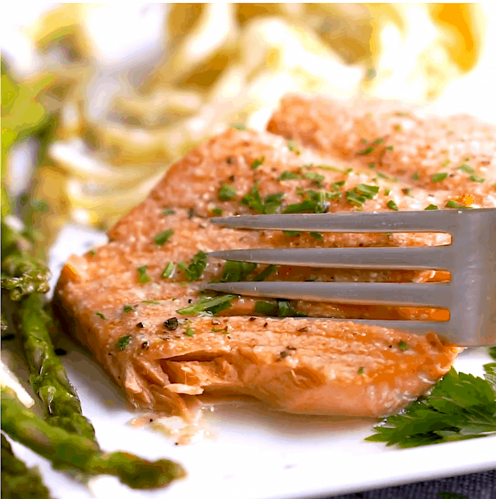 fork pressing into juicy broiled salmon