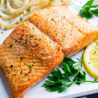 broiled salmon and fettuccini alfredo on white plate with lemon and parsley garnish