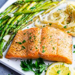 broiled salmon, sautéed asparagus, and fettuccini alfredo on white plate with lemon and parsley garnish