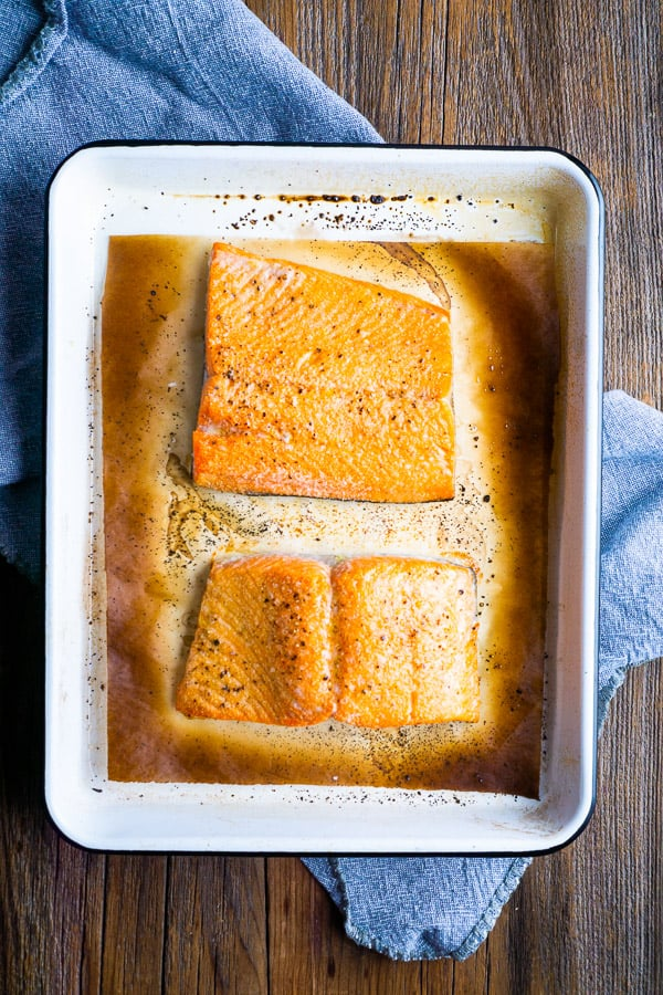 broiled salmon fillets on browned parchment-lined white baking pan on blue linen on brown table