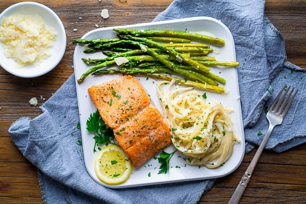 broiled salmon, sautéed asparagus, and fettuccini alfredo on white plate with lemon and parsley garnish, bowl of parmesan cheese, and silver fork
