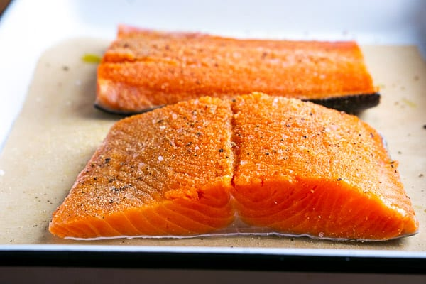 fresh salmon fillets on parchment-lined white baking pan