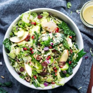 kale brussel sprout salad in white bowl on gray linen with scattered ingredients