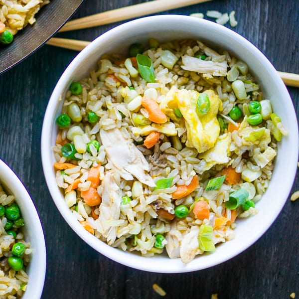 chicken fried rice in white bowl with chopsticks on grey background