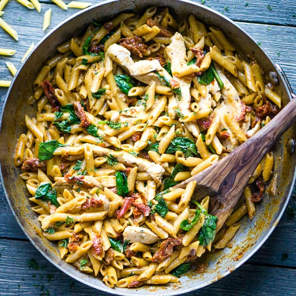 wooden spoon scooping chicken penne alla vodka in stainless skillet