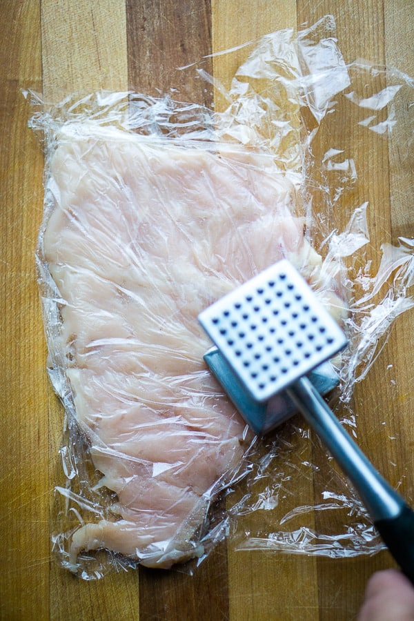 raw chicken breast being tenderized with a stainless mallet