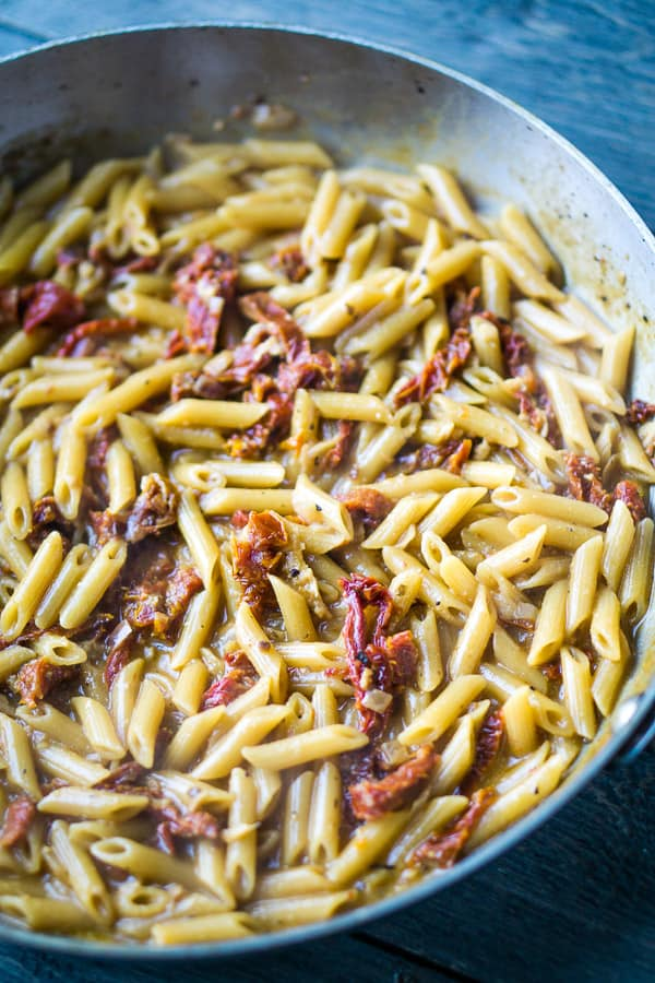 sun-dried tomatoes and cooked penne pasta noodles in a stainless skillet