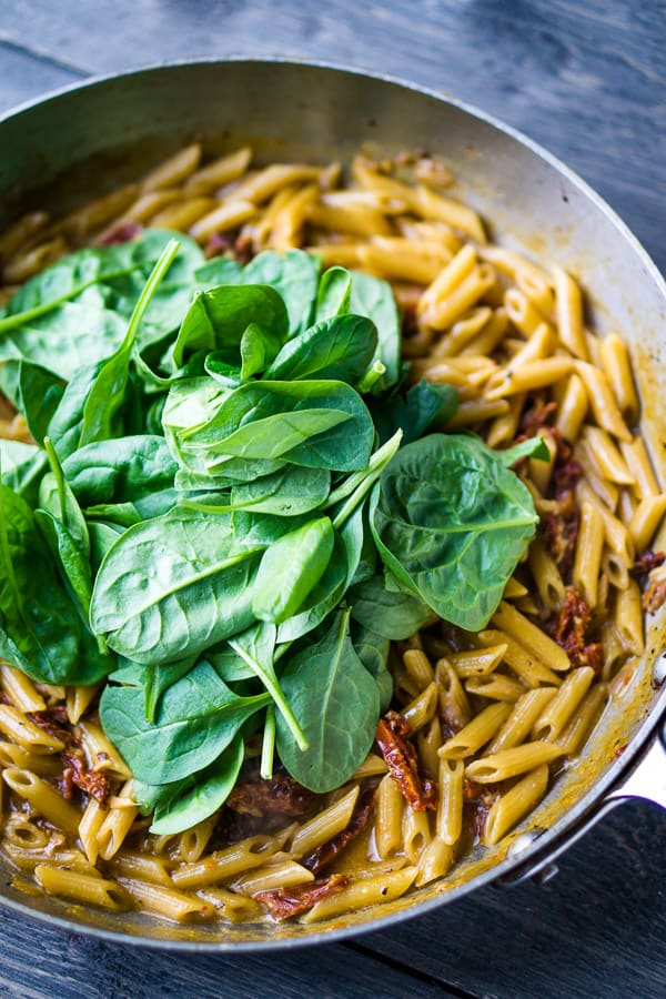 fresh spinach piled on a bed of cooked penne pasta and sun-dried tomatoes in a stainless skillet