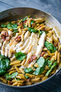 sliced chicken laying on a bed of fresh spinach, cooked penne noodles, and sun-dried tomatoes in stainless skillet