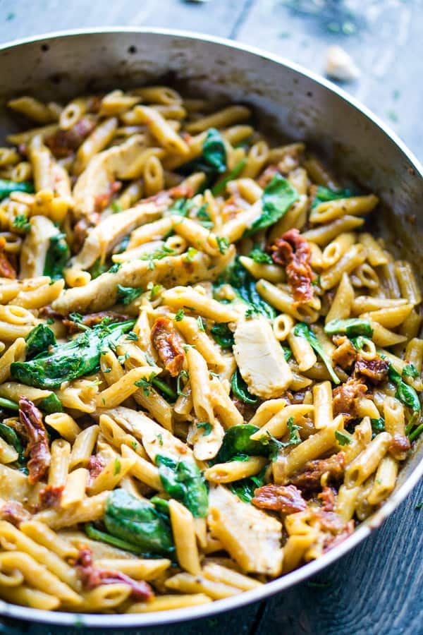 sliced chicken, fresh spinach, cooked penne noodles, and sun-dried tomatoes in stainless skillet