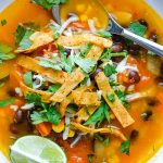 chicken tortilla soup in white bowl with spoon garnished with lime