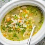 chicken vegetable soup in white crockpot slow cooker with soup ladle