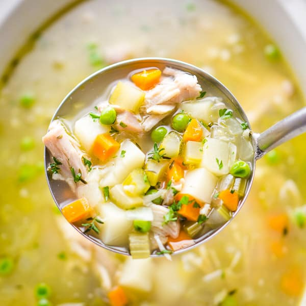 soup ladle full of chicken vegetable soup above white crockpot slow cooker full of soup