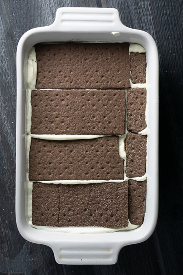 Chocolate graham crackers layered in icebox cake in white ceramic dish on gray wood background