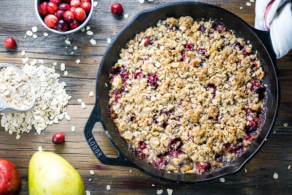 Cranberry apple crisp in iron skillet on wood surface with fresh cranberries, oats, a pear, and apple on wood surface