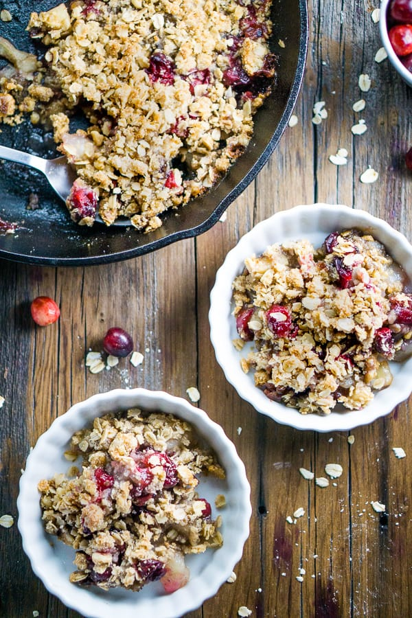 Cranberry apple crisp plated and in iron skillet on wood surface with fresh cranberries, oats, a pear, and apple on wood surface