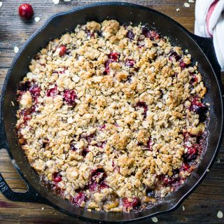 Cranberry apple crisp in iron skillet on wood surface