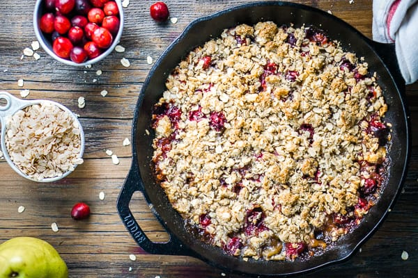 cranberry apple crisp in iron skillet on wood background with whole cranberries and whole oats in measuring cups
