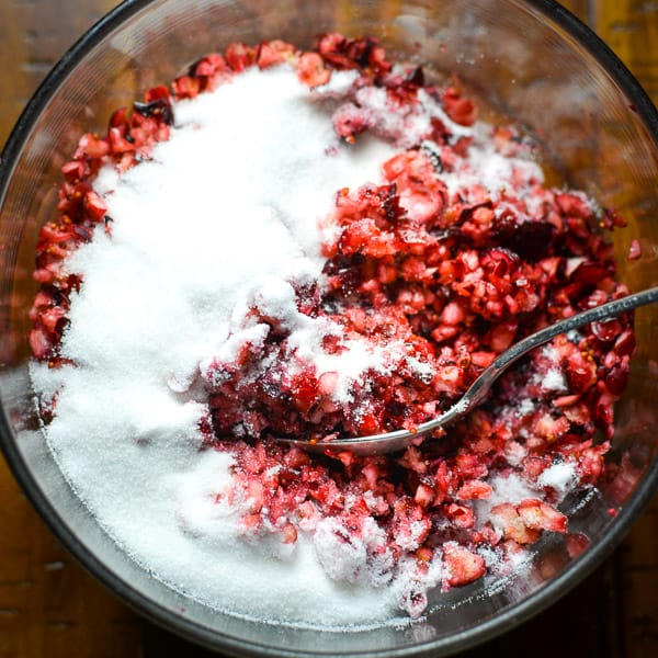 Raw cranberries, pomegranate seeds, and sugar being mixed together with a spoon
