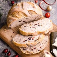 sliced cranberry walnut bread loaf on cutting board next to Christmas decorations