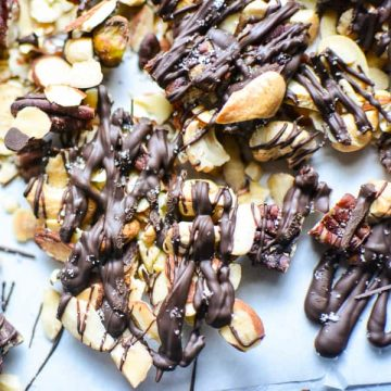 salted chocolate drizzled mixed nuts on white parchment paper