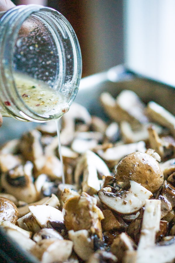 pan of marinated mushrooms with Italian dressing being poured over them