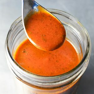 glass jar of red enchilada sauce with a spoon portion