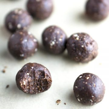 chocolate energy bites scattered on off-white background