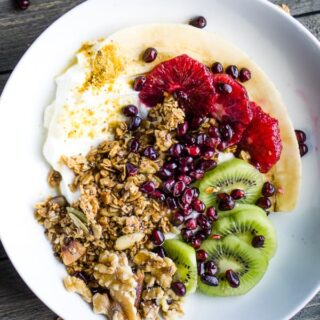 fresh fruit, granola, and walnuts in white bowl on gray wooden table