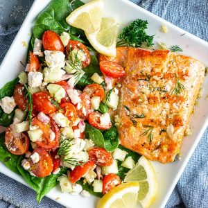 Grilled salmon and cucumber salad with lemon garnish on white plate on blue linen