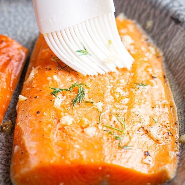 Silicone pastry brush spreading garlic butter on salmon fillet on gray pie plate