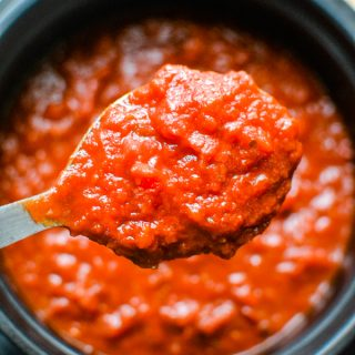 close up of red homemade tomato sauce on serving spoon over pot of sauce