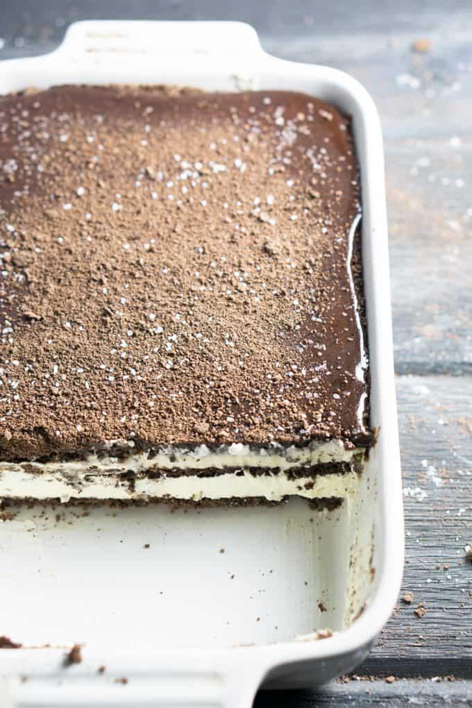 Easy, no bake refrigerator dessert! Icebox Chocolate Eclair Cake with chocolate grahams, vanilla pudding & whipped topping, chocolate sauce, and Kosher salt flecks! thekitchengirl.com #refrigeratorcake #sexinapan #nobakedessert #gameday #summerdessert #chocolate #puddingcake #iceboxcake