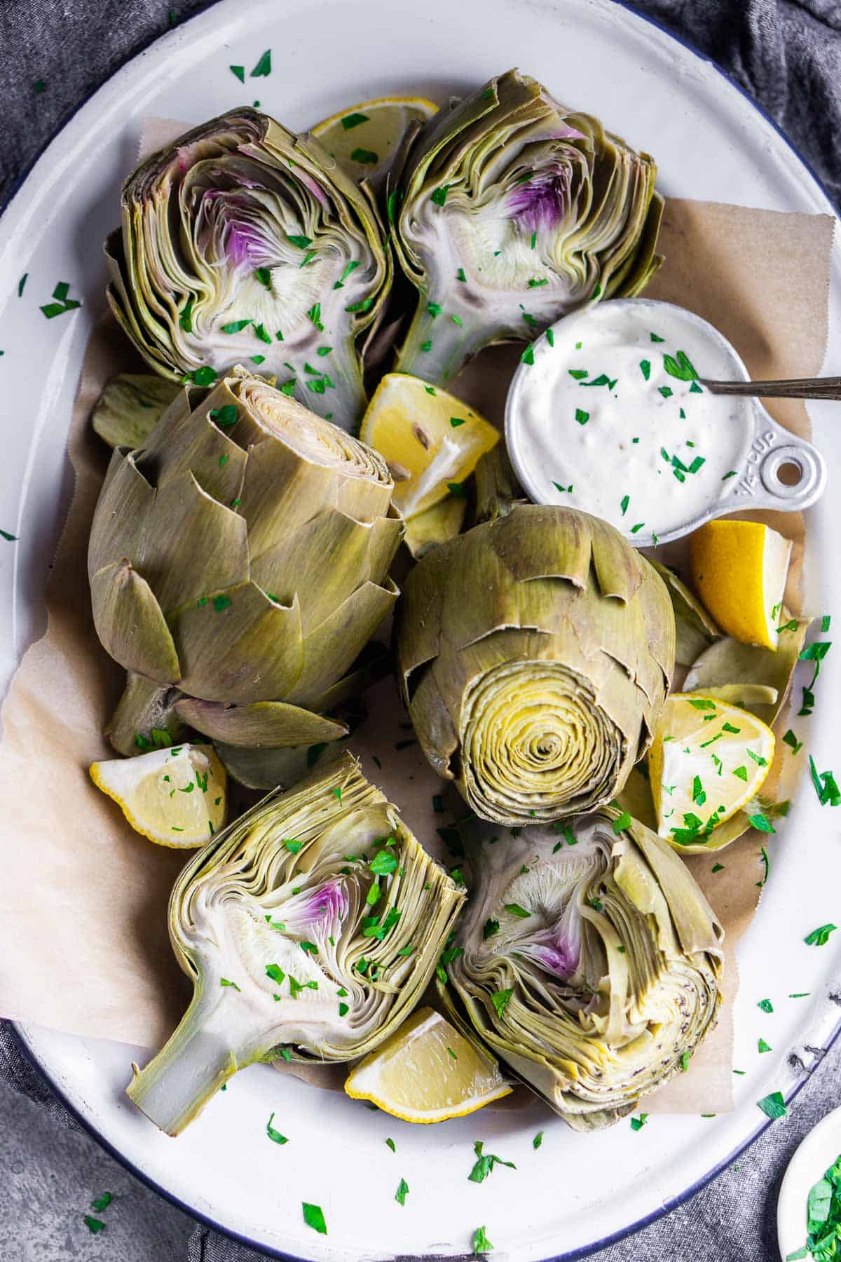steamed artichokes on white platter with dipping sauce and lemon wedges